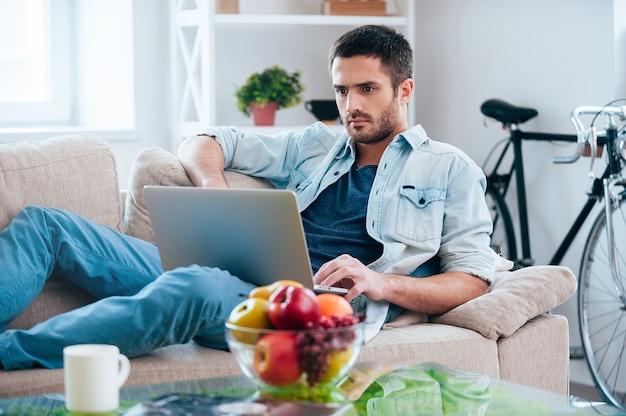Freizeit zu hause genießen. schöner junger mann, der am laptop arbeitet, während er zu hause auf der couch liegt