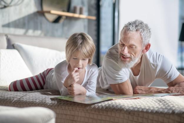Freizeit zu hause. interessierter aufmerksamer bärtiger vater des kindes und des erwachsenen, der auf bett liegt und buch liest