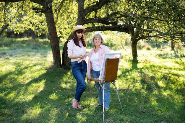 Freizeitaktivitäten im freien, kunst und malerei zusammen. glückliche blonde dame im ruhestand, die ein bild auf einer staffelei malt, zusammen mit ihrer jungen hübschen tochter im strohhut, im schönen grünen sonnigen park
