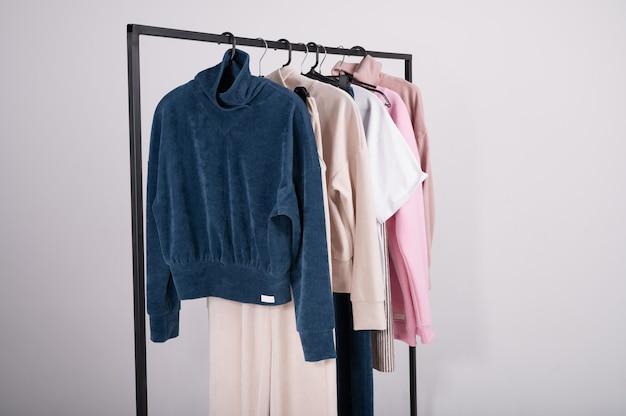 Freizeitmode der frühlingsmode, die an einem gestell hängt. stilvolle weibliche t-shirts, hoodie, hosen auf kleiderbügel