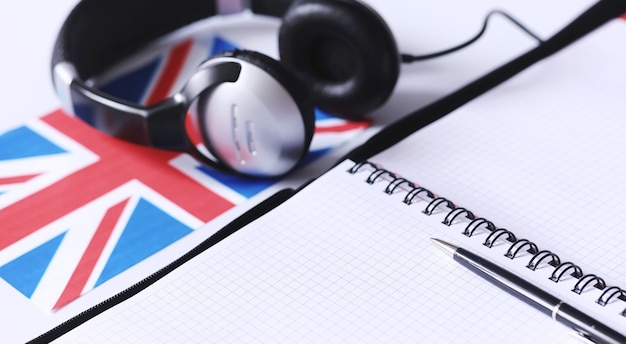Fremdsprachen lernen. notizblock für einträge und eine flagge. sprachkurse, hörprobe.