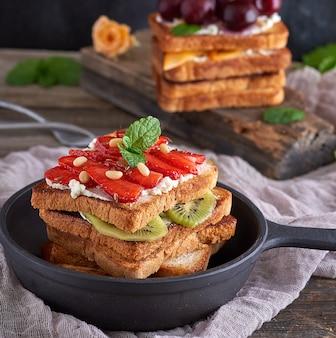 French toast aus weißbrot mit hüttenkäse, erdbeeren, kiwi in einer runden bratpfanne aus schwarzem gusseisen