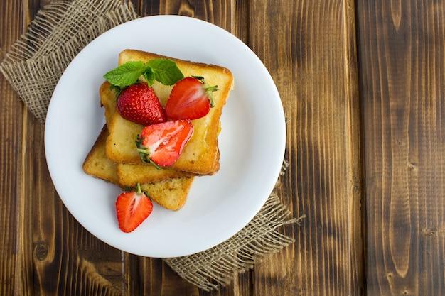 French toast mit erdbeeren in der weißen platte auf der rustikalen holzoberfläche.
