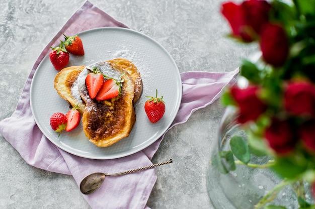 French toast mit erdbeeren. vase mit rosen.