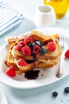French toast mit sirup und himbeeren zum frühstück auf teller serviert. nahaufnahme