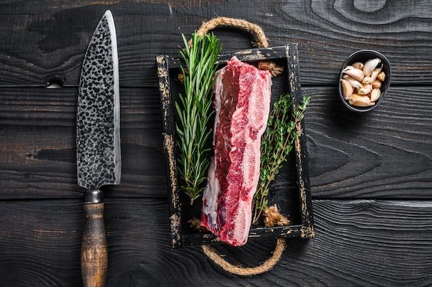 Fresh raw kalbfleisch kurze rippen in einem holztablett mit kräutern