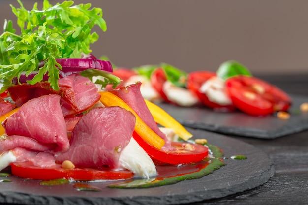 Fresh tasty persimmon salat mit rucola, parmaschinken, olivenöl und kräutern. herbst, winter gesunde ernährung
