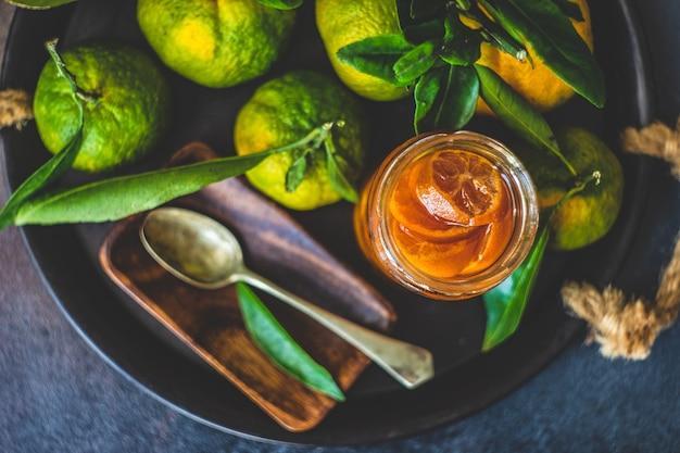 Freshmade mandarinenfruchtkonserve auf rustikalem hintergrund mit kopienraum