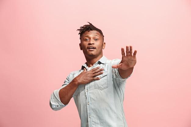 Freude. afroamerikanisches männliches vorderporträt in halber länge, isoliert auf rosa studiohintergrund. junge, emotionale, lächelnde, überraschte mannstellung. menschliche emotionen, gesichtsausdruckkonzept. trendige farben