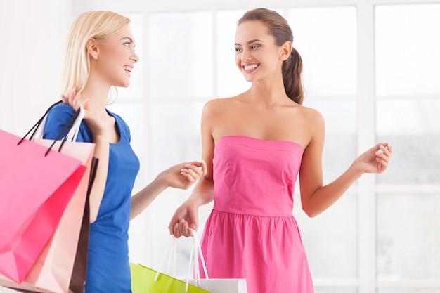 Freude am einkaufen. zwei fröhliche junge frauen in kleidern, die zusammen gehen und einkaufstüten halten