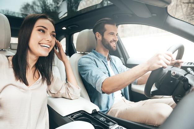 Freude am reisen. schönes junges paar, das auf den beifahrersitzen sitzt und lächelt, während ein gutaussehender mann ein auto fährt?