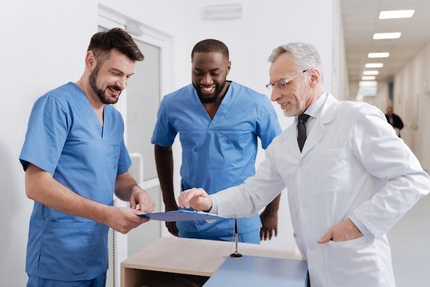 Freude an der diskussion mit kollegen. lächelnder professioneller alter sanitäter, der im krankenhaus arbeitet und den täglichen bericht überprüft, während er sich mit kollegen unterhält