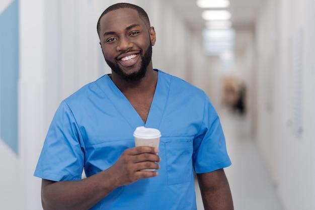Freude an details. freundlicher junger afroamerikanerpraktikant, der im krankenhaus steht, während kaffeepause genießt und die tasse kaffee hält