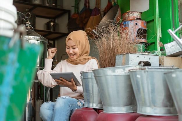 Freude der verkäuferin, die tablette mit erhobener hand verwendet, wenn sie im geschäft für haushaltsgeräte überrascht wird