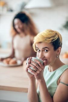 Freude. fröhliche junge erwachsene frau mit kurzer frisur, die kaffee trinkt, freudig und dunkelhäutige freundin in der ferne schauend