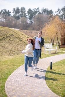 Freude, geh. lachende energische junge frau und mann in bequemer freizeitkleidung, die an einem sonnigen tag in verspielter stimmung im freien laufen running