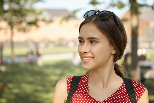 Freude, glück, sommer, urlaub und reisekonzept. freudige attraktive junge frau mit sonnenbrille auf dem kopf und rucksack lächelnd fröhlich, aufgeregt beim sightseeing in einer europäischen stadt