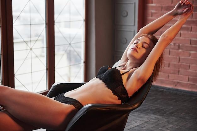 Freude mit geschlossenen augen und erhobenen händen. heißes wunderschönes junges mädchen in unterwäsche, das auf dem stuhl drinnen sitzt