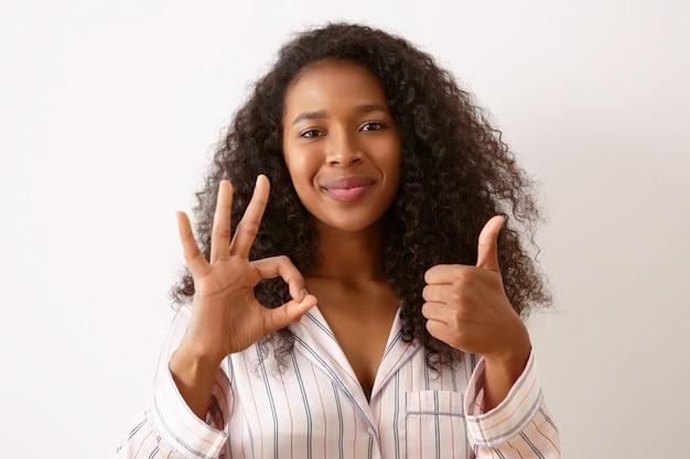 Freude, positivität und körpersprache. schönes glückliches junges mulattenmädchen mit dem gelockten schwarzen haar, das isoliert gekleidet in seidenpyjamas aufwirft, daumen hoch geste macht und ok zeichen zeigt, lächelnd
