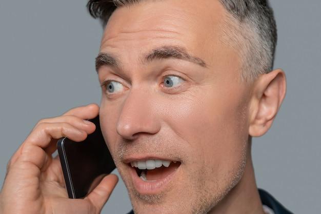 Freude, überraschung. nahaufnahme des freudigen überraschten mannes mit grauen augen, der auf dem smartphone spricht