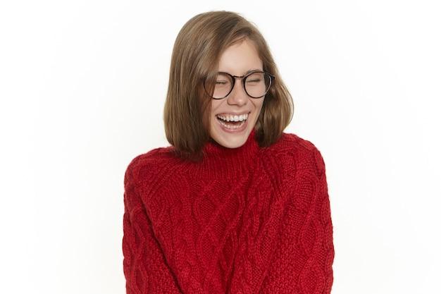 Freude und glückskonzept. hübsches mädchen in der stilvollen brille und im warmen kuscheligen pullover, die spaß drinnen haben, lustige geschichte oder witz genießen, gute laune haben. attraktive junge frau, die laut lacht