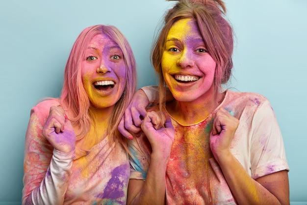 Freudig erfreute weibliche models ballen die fäuste, genießen das feiern der farbe, lachen glücklich, zeigen weiße zähne, verschmiert mit farbigem puder, isoliert über der blauen wand. fröhliche holi festivalfeier