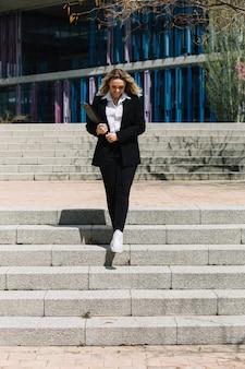 Freudig geschäftsfrau gehen die treppe hinunter in die stadt