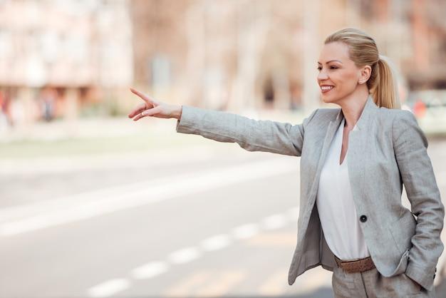 Freudig geschäftsfrau mit erhobenen hand für ein taxi.