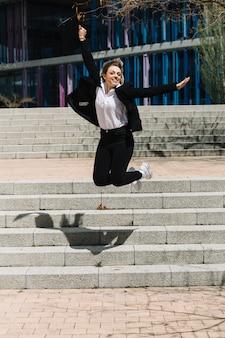 Freudig geschäftsfrau springen vor der treppe