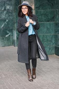 Freudig lächelnde junge frau mit brünetten haaren im langen grauen mantel, der auf straße in der stadt geht. schwarze brille, hut, blaues hemd, luxusaussicht, fröhliche stimmung, modische geschäftsfrau.