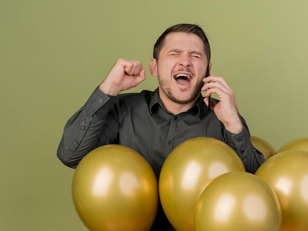 Freudig mit geschlossenen augen junger party-typ, der schwarzes hemd trägt, das zwischen luftballons steht, spricht am telefon und zeigt ja-geste, die auf olivgrün isoliert wird