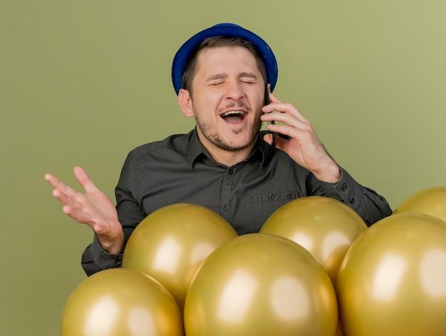 Freudig mit geschlossenen augen junger party-typ, der schwarzes hemd und blauen hut trägt, der hinter luftballons steht, spricht am telefon und verbreitet hand lokalisiert auf olivgrün