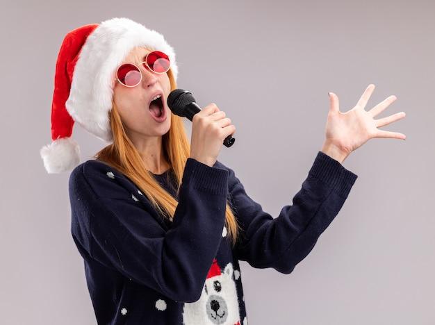 Freudig mit geschlossenen augen junges schönes mädchen, das weihnachtsmütze und brille singt, die auf mikrofonverbreitungshand lokalisiert auf weißem hintergrund singen