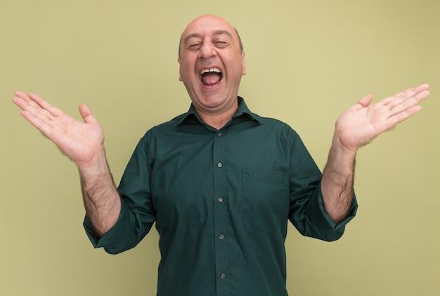 Freudig mit geschlossenen augen mann mittleren alters, der grünes t-shirt trägt, das auf olivgrüner wand isolierte hände verbreitet