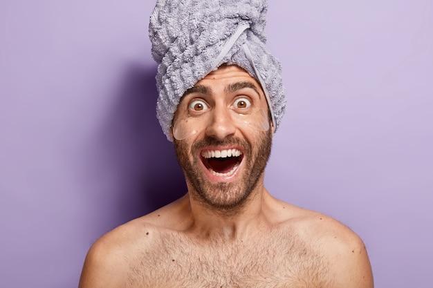 Freudig überraschter mann mit pads unter den augen, steht hemdlos vor lila hintergrund, trägt handtuch auf dem kopf, kümmert sich um die gesichtshaut