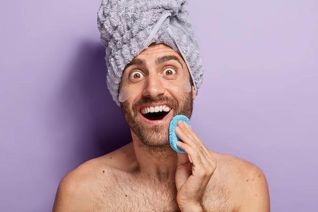 Freudig überraschter mann will glatte haut haben, wischt gesicht mit kosmetischem schwamm ab, trägt silikonpflaster unter den augen auf