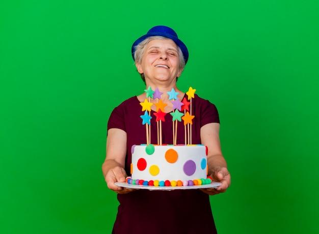 Freudige ältere frau, die partyhut trägt, hält geburtstagstorte auf grün