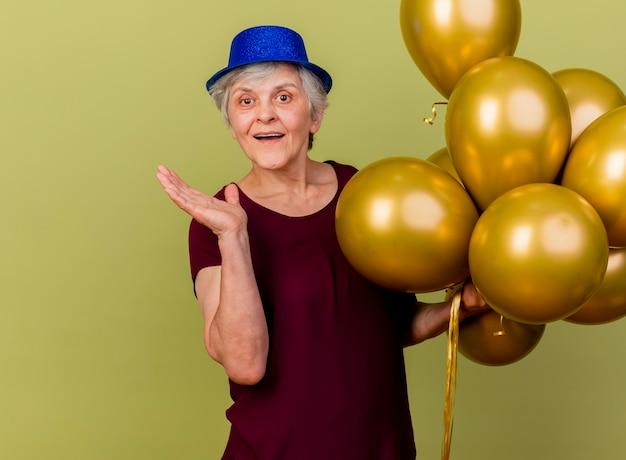 Freudige ältere frau, die partyhut trägt, steht mit heliumballons, die hand offen auf olivgrün halten