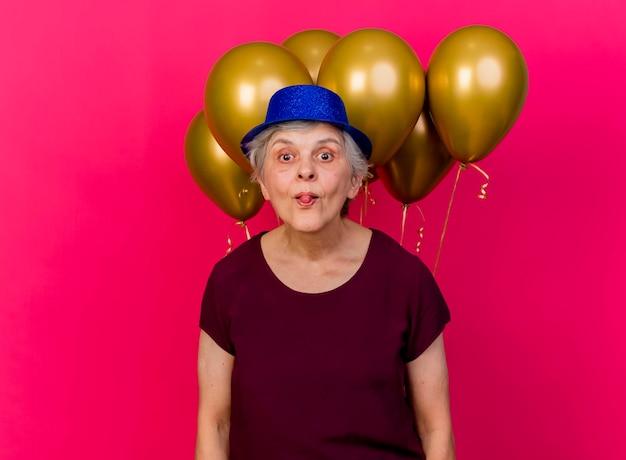 Freudige ältere frau, die partyhut trägt, steht vor heliumballons steckt zunge heraus, die kamera auf rosa betrachtet