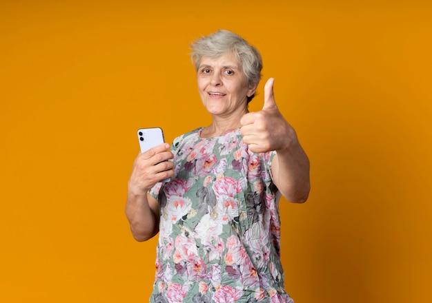 Freudige ältere frau hält telefon und daumen isoliert auf orange wand