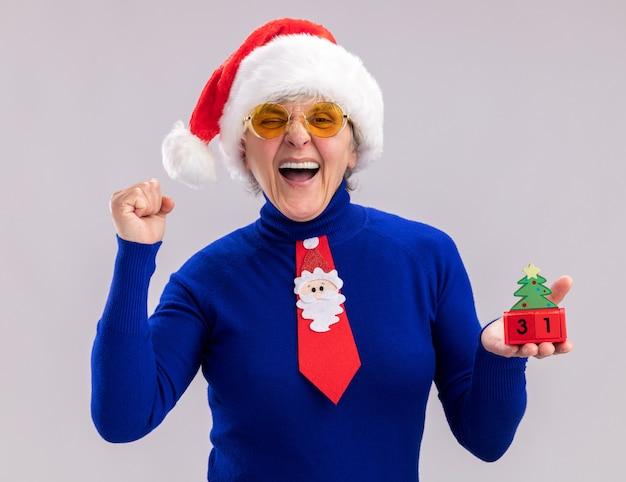 Freudige ältere frau in sonnenbrille mit weihnachtsmütze und weihnachtskrawatte, die weihnachtsbaumverzierung hält und faust lokalisiert auf weißem hintergrund mit kopienraum hält