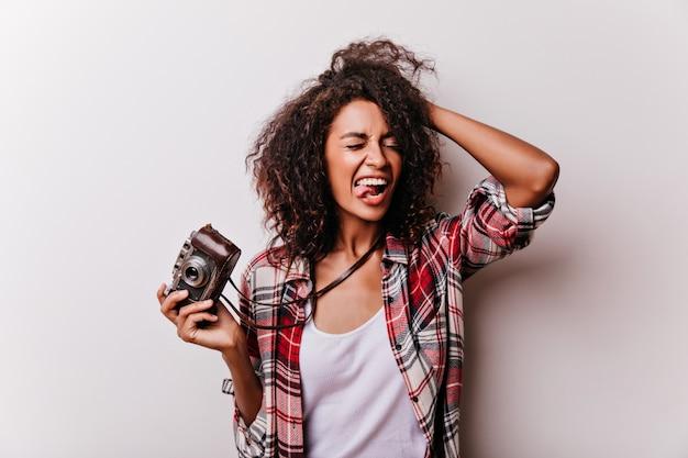 Freudige afrikanische dame, die zeit mit kamera verbringt. entzückendes schwarzes mädchen, das auf weiß herumalbert und lacht.