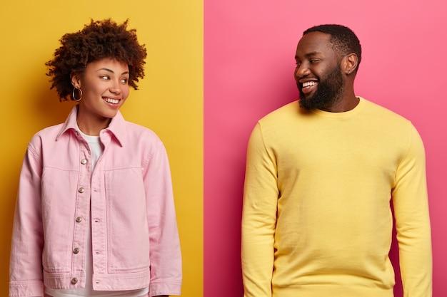 Freudige afroamerikanische frau und mann schauen sich an, haben ein breites lächeln, genießen die freizeit und freuen sich nach dem einkauf
