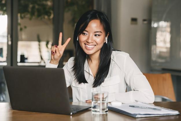 Freudige asiatische frau 20s trägt weißes hemd und ohrstöpsel lächelnd und zeigt siegeszeichen, während sie bildschirm des laptops im büro betrachten