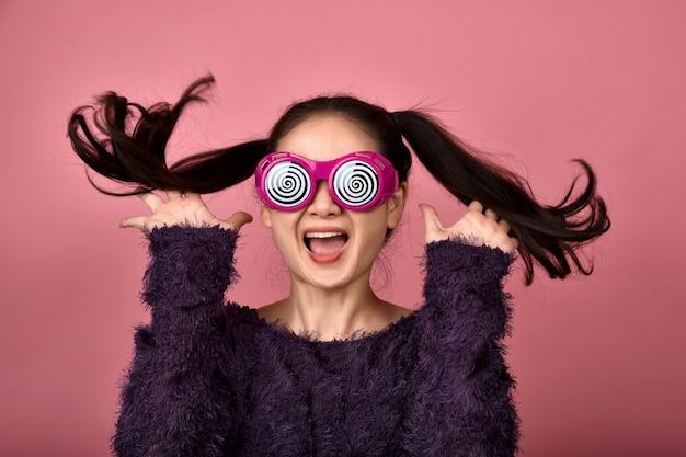 Freudige asiatische frau, aufgeregtes mädchen, das lustige brille auf isoliertem rosa hintergrund trägt, fröhliches mädchen, das mit glücksgesicht springt.