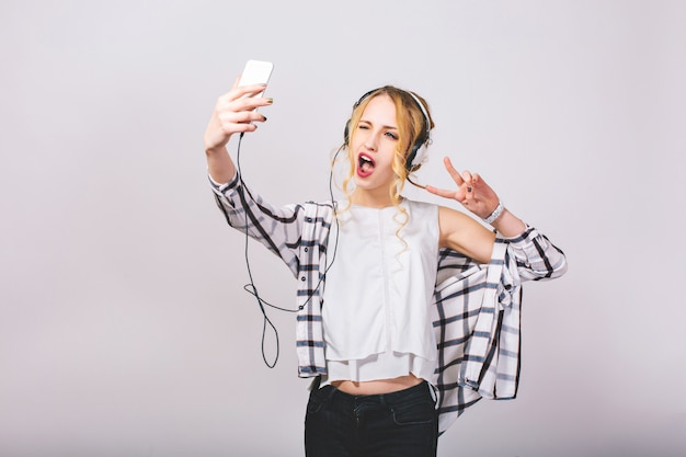 Freudige attraktive junge frau, die selfie nimmt, grimassen macht, fingerfrieden singend zeigt. fröhliches blondes mädchen, das spaß mit smartphone hat. helle emotionen. verrückte partyzeit. isoliert.