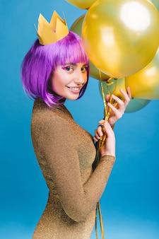 Freudige attraktive junge frau mit geschnittenem lila haar, das spaß mit goldenen luftballons hat. krone auf dem kopf, make-up mit lametta, luxuriöses modisches kleid, neujahrsparty feiern.