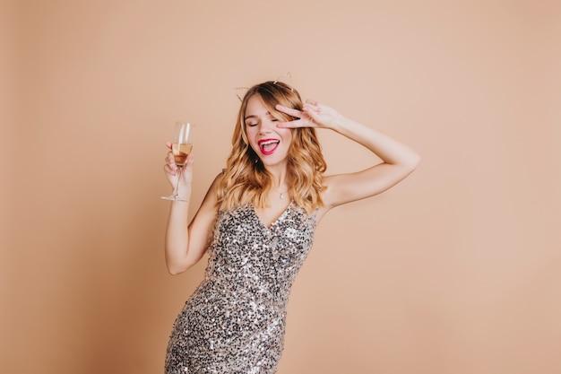 Freudige blonde frau im luxuskleid lustiges tanzen auf der party und champagner trinkend