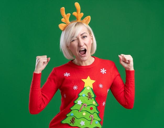 Freudige blonde frau mittleren alters, die weihnachtsrentiergeweih-stirnband und weihnachtspullover trägt, die kamera betrachten, die zwinkert, ja-geste lokalisiert auf grünem hintergrund tut