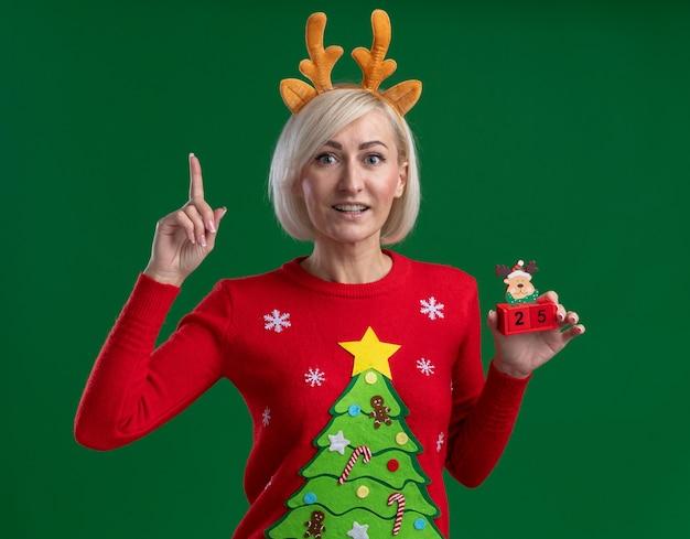Freudige blonde frau mittleren alters, die weihnachtsrentiergeweih-stirnband und weihnachtspullover trägt, die weihnachtsrentierspielzeug mit datum betrachten, das kamera zeigt, die lokal auf grünem hintergrund zeigt